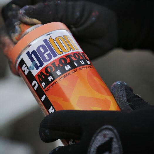 Sfeerbeeld van handen die de Molotow beschermende handschoenen dragen en een fles spray paint in de handen heeft. Molotow bescherming handschoenen vooraanzicht in het zwart/ donkergrijs. De protective gloves geven optimale bescherming en zijn perfect voor het gebruik bij graffiti en streetart, omdat ze de handen beschermen tegen spray paint.